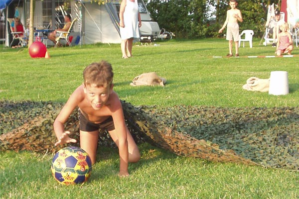 A boy with a ball is doing our temporary assault course